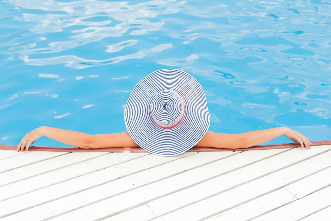 summertime photo of woman at the pool with a big round hat on